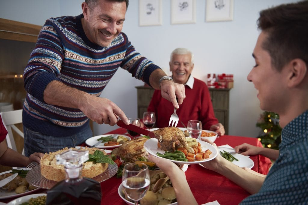 Father serves dinner at Christmas Eve